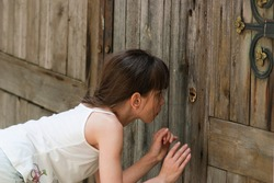 The child peeps through a keyhole. The little girl (eight years old) looks through a keyhole of old wooden gate. Outdoors