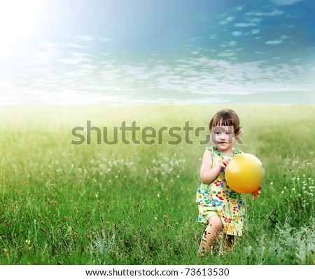 The child playing a ball on the meadow filled in with the sun - stock photo