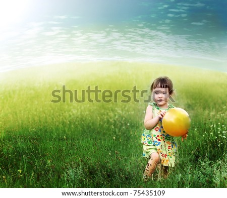 The child playing a ball on the meadow filled in with the sun
