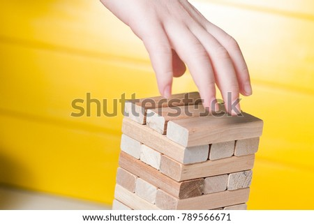 The child plays in board game falling tower of wooden blocks #789566671