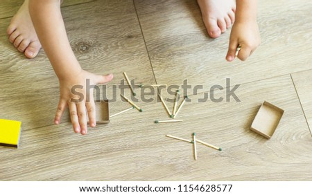 The child plays with matches, matches matches into boxes, fire, danger, ignition