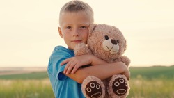 The child plays with the Teddy bear. Best friends. Little boy hugs his favorite soft bear toy on the playground. Plush toy in the hands of kid in summer park. Kid plays with a toy and dreams outdoors.