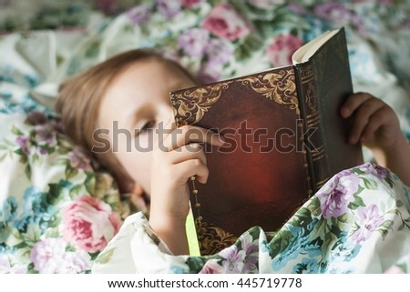 The child reads east fairy tales. To read the book. Color pastel linen. Development of the child. Clever child .  Fairy tales for the nigh t . Happy childhood .To read lying in a bed Сток-фото ©