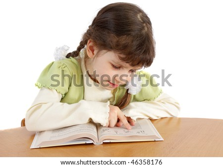 The child reads on a white background, is isolated.