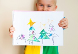 The child shows his child's drawing. Three Christmas trees decorated with balls. Iridescent clothes. Beige background.
