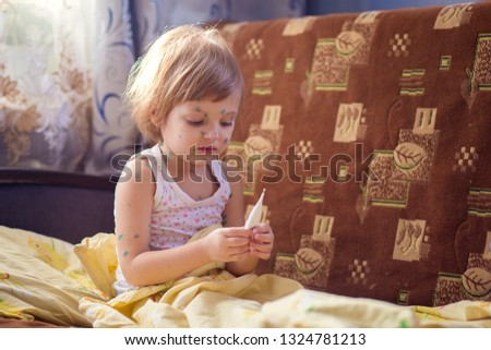 The child sick chicken pox sits in a bed and holds the thermometer in hand.