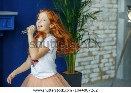 The child sings the song in the microphone. Very long hair. The concept is childhood, lifestyle, music, singing, listening, hobbies. #1044807262