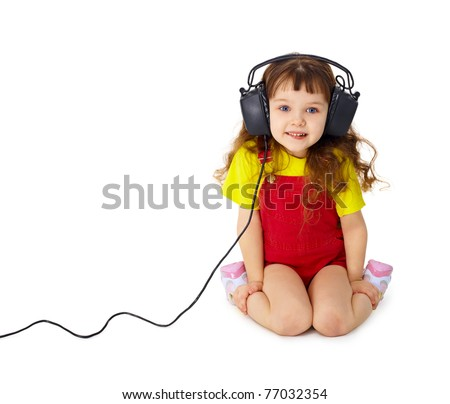 The child sits and listens attentively to the music isolated on white background