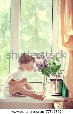 The child sits at a window