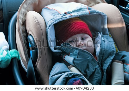 The child sits in a safety seat on forward sitting of the car.