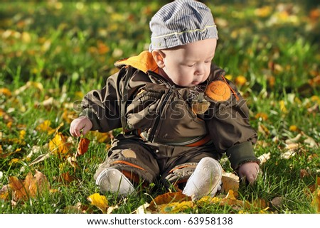 The child sits on a green grass