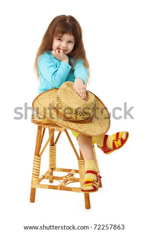 The child sits on an old wooden chair with a straw hat in hand isolated on white background