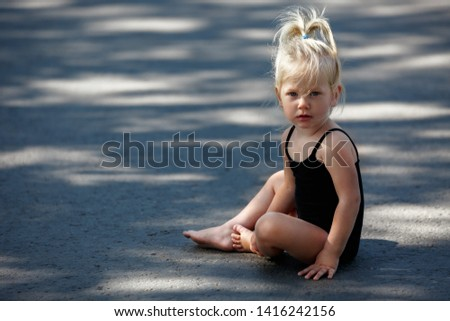 the child sits on the road. Little blonde girl posing sitting on the asphalt barefoot #1416242156