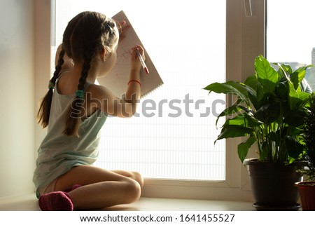 The child sits on the windowsill and ponders draws in the album.