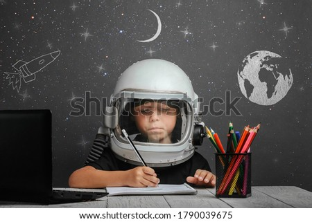 the child studies remotely at school, wearing an astronaut's helmet. back to school Photo stock ©