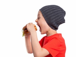 The child takes an appetising bite of a hamburger. A beautiful European boy 6 years old is going to eat fast food. Happy child. Snack. Favorite children's food.