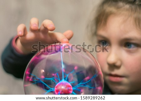 The child touches the plasma ball with his finger. Selective focus.