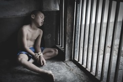 The child was tied up with a rope and was in a cell. Stop violence against children, child labor, human rights, human trafficking