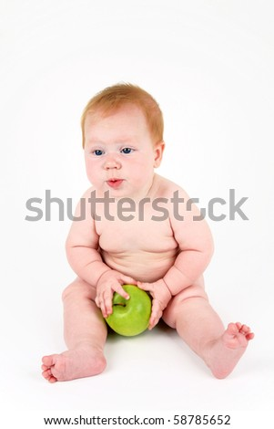 The child with a green apple in hands on a white background