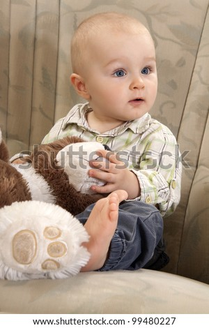 The child with amazed face is sitting on a couch and playing with teddy bear
