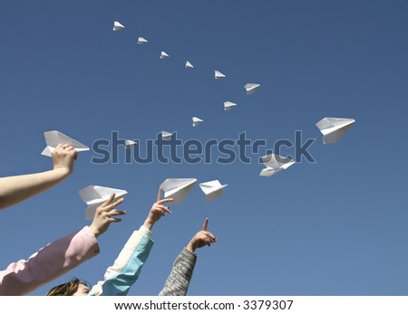 The Children hands send skyward small paper airplanes.