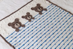 The children's plaid is made in a fairy-tale theme. The cover is crocheted in pastel colors, different patterns and with applique. A family of three teddy bears sleeps in bed under