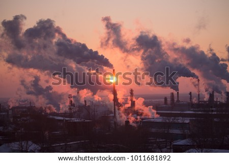 the chimneys of a refinery with smoke and steam with the pink and yellow sunset on the background