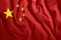The Chinese flag is flying in the wind. Colorful national flag of China. Patriotism, patriotic symbol.