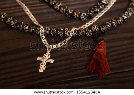 The Christian Orthodox breastplate with chain and Islamic rosary made of wooden beads and red tassels are intertwined. concept art friendship of religions between christianity and islam