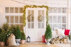 The Christmas porch is decorated with small Christmas trees and lanterns. Bench with pillows near the front door of the house