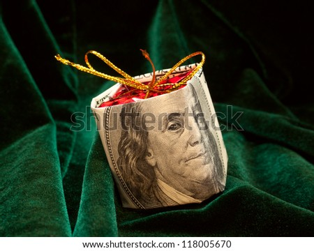 The Christmas toy wrapped in the dollar bill on the background from green velor