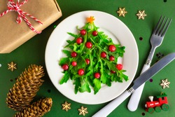 The Christmas tree arugula salad on white plate with knife and fork on green background. Flat lay. Vegetarian concept