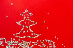 The Christmas tree is lined with rhinestones on a red background. The view from the top.