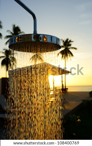 The chrome shower next to the swimming pool with silhouette coconut tree and sunrise background in thailand.