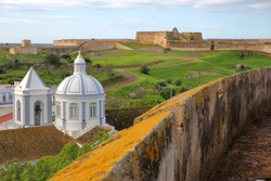 The church and the village of Castro Marim viewed from the castle and with Sao Sebastiao fort in the background, Castro Marim, Algarve, Portugal