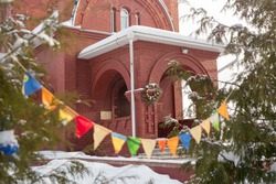 The church is visible from behind the garlanded trees. The Orthodox celebration of the winter Christmas holidays. Orthodox Epiphany celebrations.  The Church is of red brick. Michanovichi  Belarus