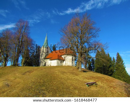 The church of St. Mohor and Fortunat at the top of Osolnik hill in the hills of Polhov Gradec in Slovenia with leafless trees on the side and a meadow in front