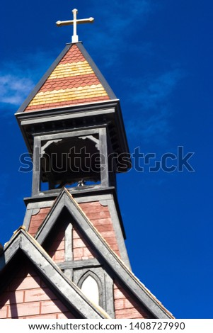 The church steeple colorful red and orage steeple against a dark blue sky with a cross at the top an vintage church