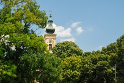 The church tower that breaks through the panorama of the green canopy of the park.  Orthodox and Catholic churches.  The bell tower of the old cathedral with a clock on the tower.  Church gate.