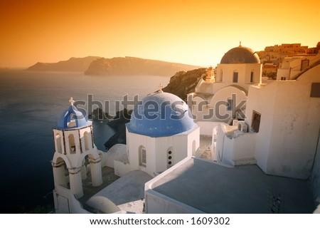 The churches, caldera and village at Oia, Santorini, under a dramatic, surreal sky.