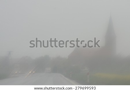 The city disappears in the fog and rain storm and it is difficult to drive a car.