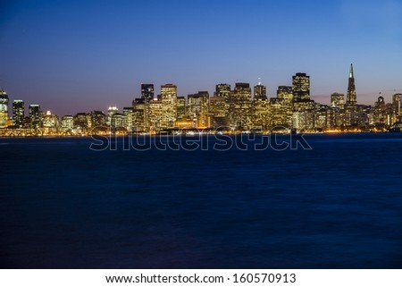 The city lights of San Francisco at twilight with the Bay Bridge on the left.