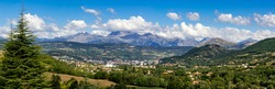 The city of Gap in the Hautes Alpes with surrounding mountains and peaks in Summer. Panoramic. Southern French Alps, France