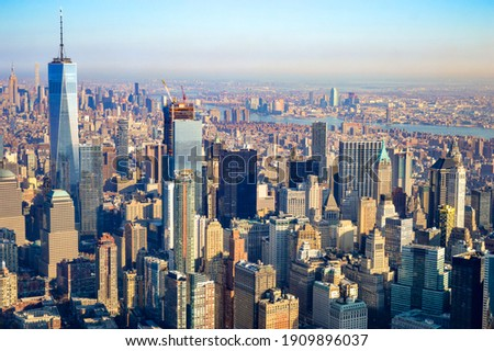 The city skyline of New York City in USA, United States on a cloudy, blue sky day with iconic buildings  from aerial, point of view.