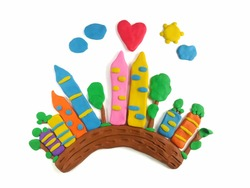 The city with fresh air is made from colorful clay plasticine on white background, many tall buildings and trees beneath the bright sky are beautiful town dough