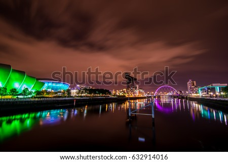 The cityscape of Glasgow city with three landmarks which are The Clyde Arc Bridge, Finnieston Crane and SEC Armadillo Building at the night time.