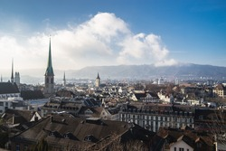 The cityscape of Zurich Switzerland with building roofs and church steeples under a cloudy blue sky