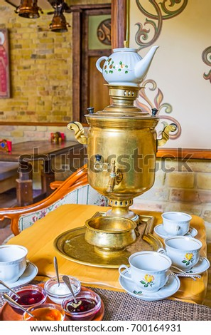 The classic Russian tea ceremony with antique brass samovar in traditional cafe. #700164931