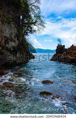 The clear beach turquoise blue water of Green Bay, Meru Betiri National Park, Banyuwangi, East Java, Indonesia, with rocks on the shore 商業照片 ©