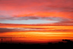 The clear blue reddish orange, blue and purple sky at the sunset time with the silhouette shapes of buildings creates the sense of calmness, meditation, beauty of natur.